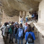 Our tour group walking past a dwelling with a balcony and climbing up a rock with foothold carved into it.