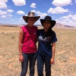 Jess and Samita with cowboy hats for shade, while herding sheep