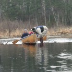 Prof. Val Hershberger paddles as Junior Sunday Mahaja pulls their canoe over a beaver dam.