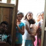 Vasanth (left) and women from the village look on while the chicha is being prepared