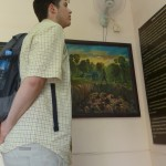 Joel with a painting by Van Nath, who survived Tuol Sleng and painted portraits of the forms of torture there.