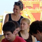 Ann with students at orientation, with a Buddhist wat in the background.