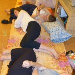 Women relax on the mats while waiting for the dishwashers to finish.