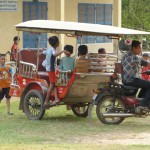 Children ride in the Graber Miller tuk-tuk while waiting for school to begin.