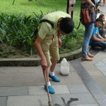 Writing poetry on the sidewalk with water, at People's Park, Chengdu.