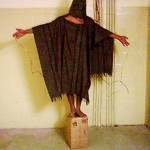One of the most widely disseminated photographs from Abu Ghraib, the Iraqi prison where U.S. military personnel tortured and shamed prisoners in 2004. The man in this image is balancing on a box in a black cape with wires attach to his extended palms and he has reportedly been told he will be electrocuted if he falls off the box.