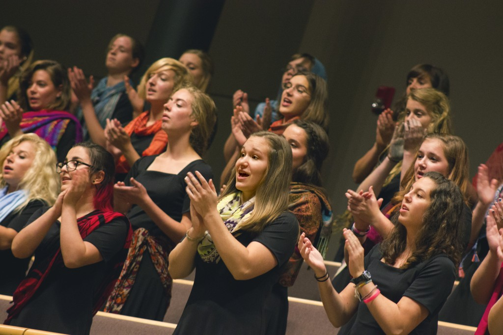 The Goshen College Women's World Music Choir performs during the homecoming weekend celebrations. During performances, members wear vibrantly colored scarves and go barefoot as a way to feel connected to the earth and to women around the globe. (Photo by Alia Munley)