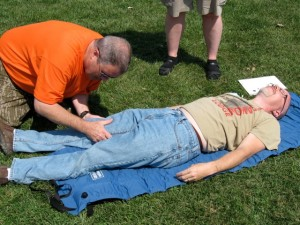 A Wilderness First Aid participant checks for a broken bone during a class simulation.