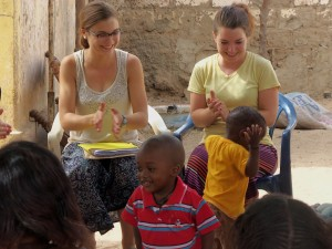 Lydia Alderfer (left), a 2013 graduate with a degree in sociology, and Maddie Ruth (right), a 2014 graduate with a degree in music and psychology, provide a beat for young dancers in Ndombo Mbodjienne, a small town in northern Senegal. The two served at an organization run by local women that processed dairy products during Study-Service Term in 2012. (Photo provided)
