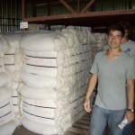 Ruben standing next to many 300-400 pound bales of organic cotton.