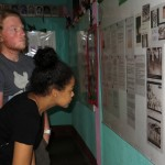 Seth and Cora look at documents and pictures of those who died during the Literacy Crusade