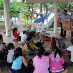 Children sit on mats to hear a story read.