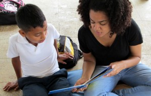 Cora helps a student read a book.