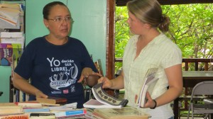 Maria Anela, the director of the library, sorts recently donated books with Becky.