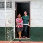 Maria with host mom in the door of their home.