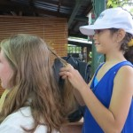 The music teacher's daughter braids Becky's hair during the practice.