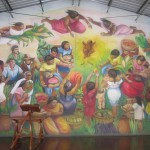 One of the many murals at Batahola Norte. This one shows the brown (indigenous) Christ child being attended by three women/angels, who bring gifts from the harvest. Sandino, Che, Archibishop Romero, and Carlos Fonseca are among the members of the community in this nontraditional Nativity scene.