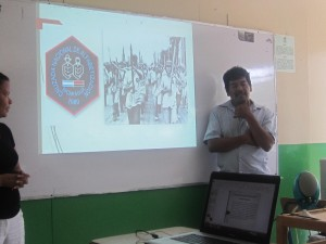 """Humberto showing the logo of the campaign and a photo of young brigadistas marching (with oversized pencils) in the """"war against illiteracy."""""""