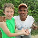 Josiah holds a crab from a local Miskito man