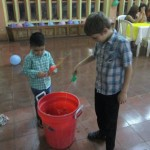 Josiah and a host family member playing a fishing game.