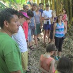 Students learn about the only fresh, clean water source in the area-part of what makes Vicente's farm so coveted.