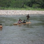 A local family crossing the river by raft