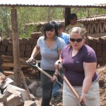 Shoveling dirt to prepare an adobe wall