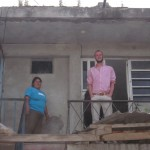 With his host mother, Feliciana, outside her home