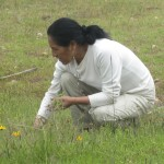 Raquel gathering herbs as we approach Roel's home