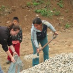 While some play soccer, others help move rock for a neighbor