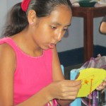 Angie, a developmentally-delayed girl, concentrates on her stitches