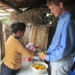 Helping his mother, Paulina, squeeze oranges for juice