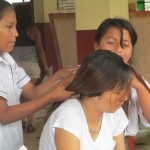 While helping one girl, two others braid her hair