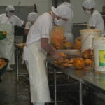 Slicing papayas for the production of a juice that features both papaya and maracuya (passion fruit)