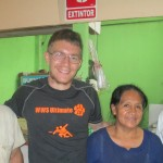 With his host father Alcides, mother Radiola and brother Lenin, in the small restaurant they operate at the local market