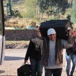 Pastor Eloy carries a suitcase to the waiting bus