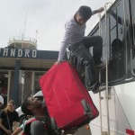 Our trusted dirver, Hugo, loads suitcases on the roof of the bus