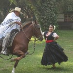 The man is mounted on a caballo de paso while the woman dances alongside the horse