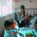Whitney helps a group of children with hand work projects