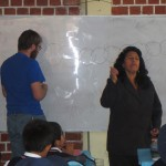 MIss Rosalia leads a song as Michael writes the day's lesson on the white board
