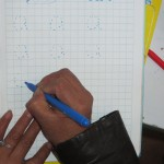 Elizabeth designing the homework assignment she'll send home with each child -- hand-printed in each student's notebook