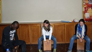 Camilo Ballumbrosio teaches Lauren and Becca how to play the cajon.