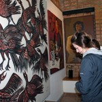 Becca examines a painting by Victor Delfin.
