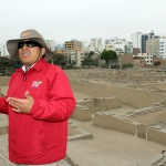 A tour guide explains the significance of the ancient Huaca Pucllana with the backdrop of modern Miraflores.