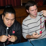Jacob and Joshua examine jewelry created by Eliana Mauriola Carrasco.