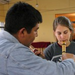 Mauro Claros Chatas teaches Lauren how to play the flute.