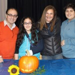 Becca's host family, the Castellanos, pose in front of the model pumpkin the students created.