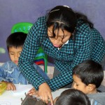 Teacher Raquel Sumari helps some children.