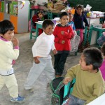 Boys perform a dance from Tarma for three classroom visitors.