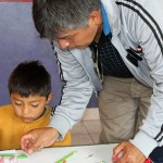 Wilfredo Villavicencio, Goshen College's service coordinator in Peru, assists a child at the Vidas preschool.